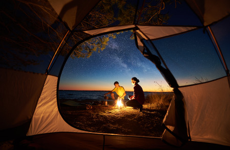 Foto de Camping on sea shore at sunset, view from inside tourist tent. Young tourist couple, man and woman preparing food on gas burner, sitting near campfire on blue sea water and starry sky background - Imagen libre de derechos