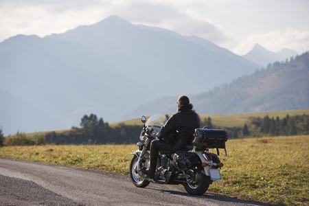 Photo pour Back view of biker in black leather jacket riding cruiser motorcycle along road on blurred copy space background of beautiful foggy mountain range and cloudy sky on bright sunny day. - image libre de droit
