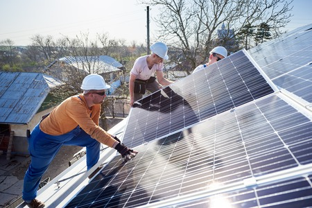 Foto de Male workers installing solar photovoltaic panel system. Electricians mounting blue solar module on roof of modern house. Alternative energy ecological concept. - Imagen libre de derechos