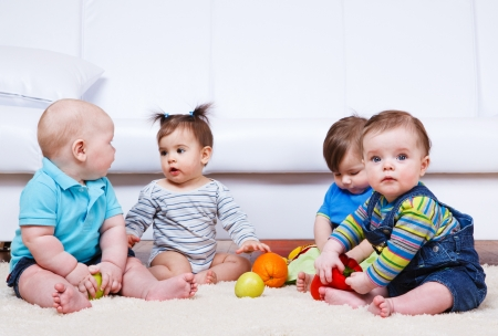 Four babies group sitting on the floor