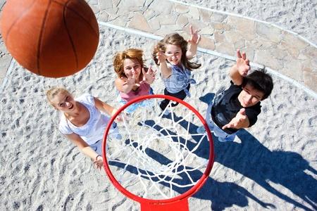 Teenagers team playing street basketball