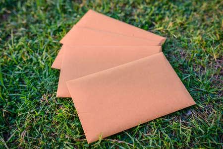 Foto de Brown envelope back  on grass background, Business Delivery concept. - Imagen libre de derechos