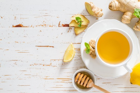 Photo for Ginger tea and ingredients on white wood background, copy space - Royalty Free Image