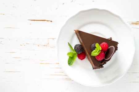 Chocolate cake slice on white plate mint berries, white background