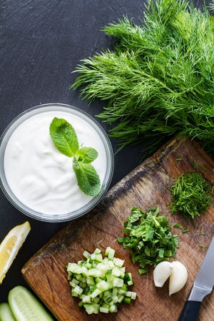 Photo for Preparing tzatziki sauce and ingredients, dark stone background, top view - Royalty Free Image