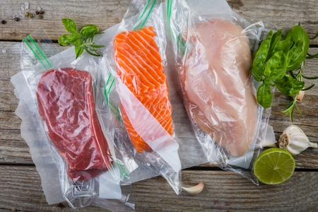 Photo pour Beef, chicken and salmon in vacuum plastic bag for sous vide cooking - image libre de droit
