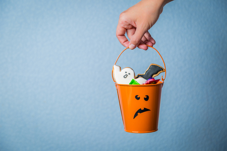 Photo for Halloween concept - hand holding basket with candies - Royalty Free Image