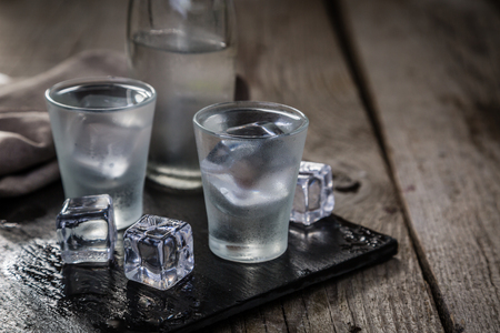Photo for Vodka in shot glasses on rustic wood background - Royalty Free Image