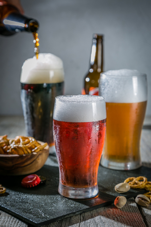 Photo pour Different types of beer on rustic wood background - image libre de droit