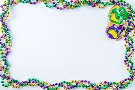 Foto de Mardi gras carnival background - beads and mask on white background, isolated - Imagen libre de derechos