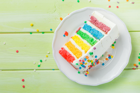 Photo for Birthday background - striped rainbow cake with white frosting - Royalty Free Image