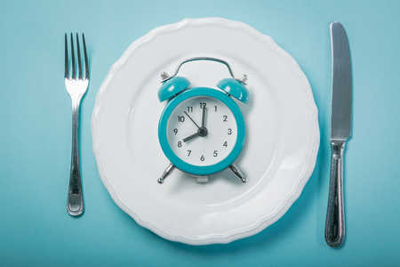 Photo for Intermittent fastin concept - empty plate on blue background - Royalty Free Image