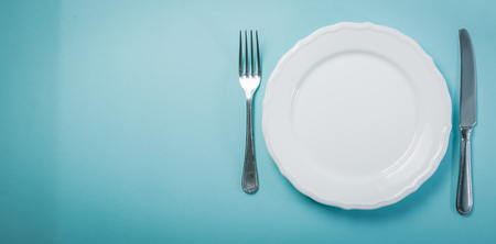 Foto de Intermittent fastin concept - empty plate on blue background - Imagen libre de derechos