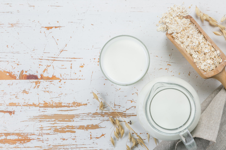 Photo for Oat milk in glass and jar on wood background - Royalty Free Image