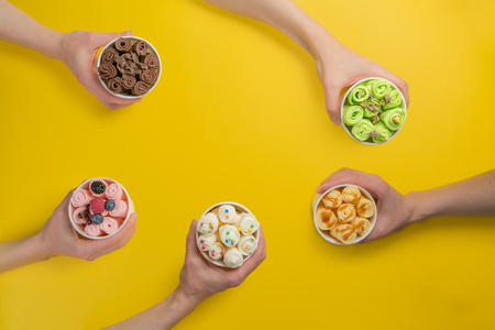 Foto de Hands holding cups with different rolled ice cream on bright yellow background - Imagen libre de derechos