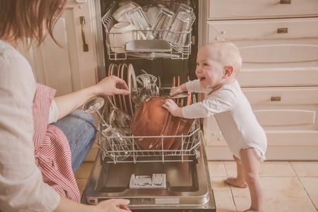 Foto de Baby gils helps mother to empty a dishwasher - Imagen libre de derechos