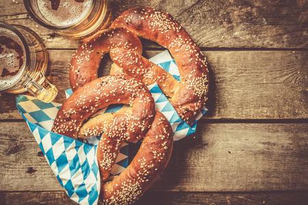 Photo pour Oktoberfest concept - pretzels and beer on rustic wood background, top view - image libre de droit