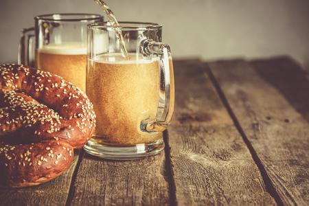 Photo pour Oktoberfest concept - pretzels and beer on rustic wood background, copyspace for text - image libre de droit