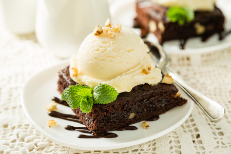Photo for Chocolate brownie with vanilla ice cream, nuts and mint, served om white plate - Royalty Free Image