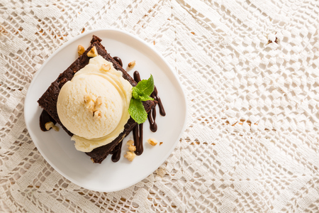 Photo for Chocolate brownie with vanilla ice cream, nuts and mint, served om white plate, copy space - Royalty Free Image