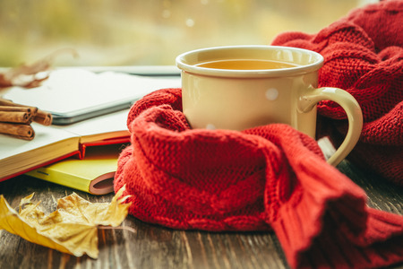 Foto de Autumn tea with scarf and leaves in front of window - Imagen libre de derechos