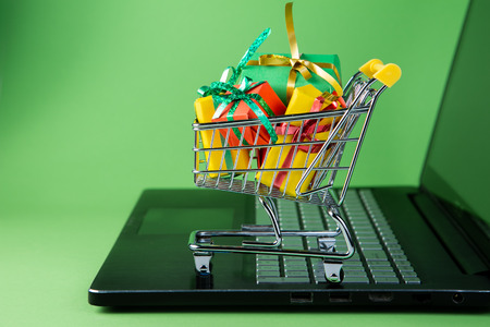Photo for Ciber monday concept - trolley cart with christmas presents on notebook - Royalty Free Image