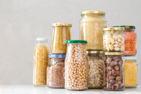 Photo for Various uncooked cereals, grains, beans and pasta for healthy cooking in glass jars - Royalty Free Image