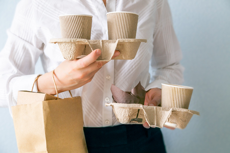 Photo for Female holding coffee containers, paper bag withfood containers. Food and coffee delivery. Intern on first job - Royalty Free Image