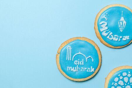 Foto de Eid Al-Adha Mubarak holiday concept - blue cookies with stenciled pictures - Imagen libre de derechos