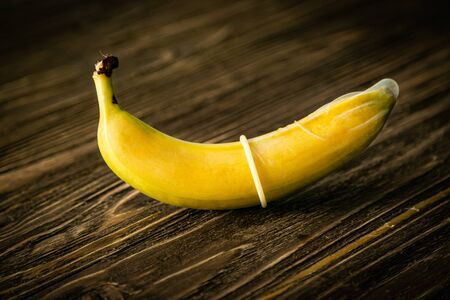 Photo for Sex education concept - banana in condom on wood background - Royalty Free Image