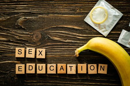 Photo for Sex education concept - letters, banana and condoms on wood background - Royalty Free Image