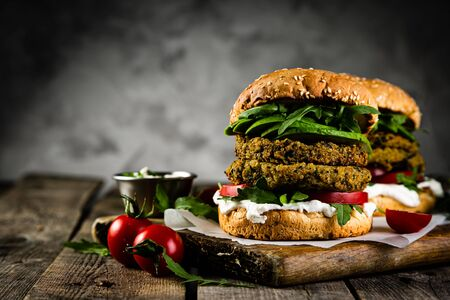 Photo for Vegan zucchini burger and ingredients on rustic wood background - Royalty Free Image