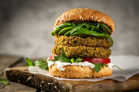 Photo pour Vegan zucchini burger and ingredients on rustic wood background - image libre de droit
