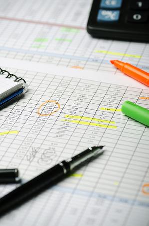 Foto de Financial calculations in a table on paper, pen, highlighter and calculator. Vertically - Imagen libre de derechos