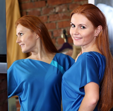 beautiful red-haired woman posing in front of a mirror