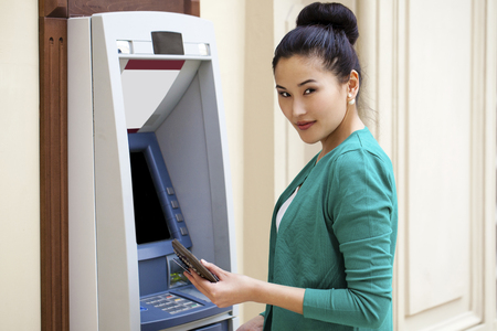 Asian lady using an automated teller machine . Woman withdrawing money or checking account balance