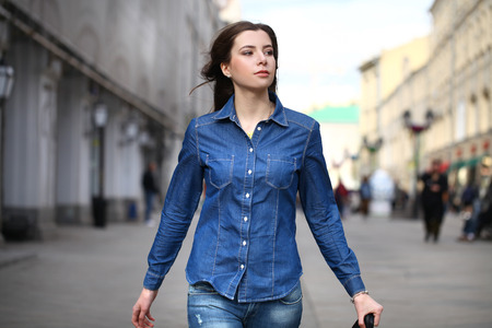 Photo for Close up Portrait of a beautiful young woman in a blue jeans shirt on the background of spring street - Royalty Free Image