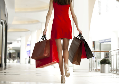 Photo for Beautiful young woman in a red dress, holding shopping bags walking in the shop - Royalty Free Image