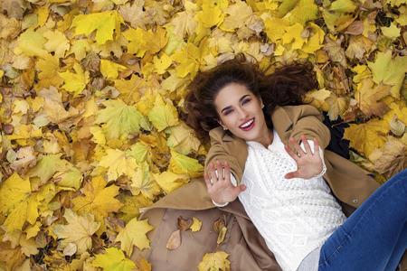 Photo pour Young beautiful girl in blue jeans lying on yellow leaves, view from above, in the autumn park - image libre de droit