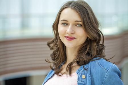 Beautiful brunette woman in blue jeans jacket, against summer street