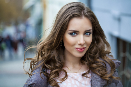 Photo for Portrait close up of young beautiful brunette woman, on spring street background - Royalty Free Image