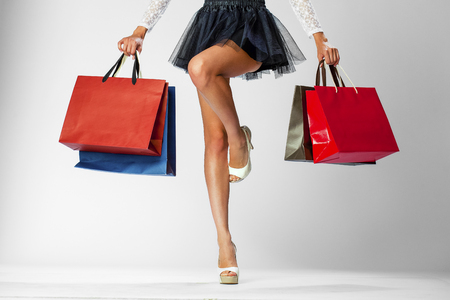 Foto für Part body, beautiful female slender legs. Sexy girl holding a paper shopping bags, isolated on white background - Lizenzfreies Bild