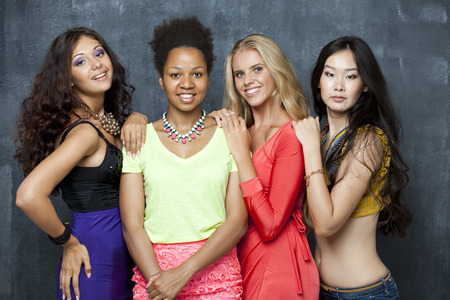Photo pour Ethnic four women face - isolated on dark wall - image libre de droit