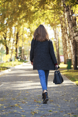 Photo for Back view. Portrait of a full length brunette woman in a gray woolen coat walking in autumn park - Royalty Free Image