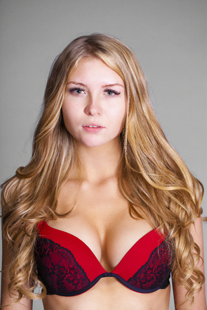 Photo pour Happy young blonde woman posing in red bra over gray background - image libre de droit