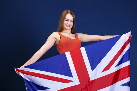 Photo pour Young beautiful girl holding a large flag of Great Britain, dark blue studio background - image libre de droit