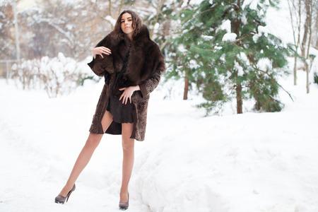 Foto de Young beautiful brunette girl in blue fur coat posing on winter park. Model wearing stylish warm clothes. - Imagen libre de derechos
