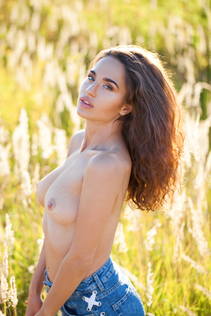 Photo pour Sexy body. Attractive brunette young brunette woman posing flirty topless at grass fields, summer outdoor - image libre de droit