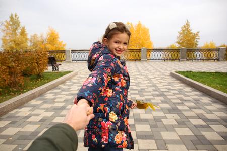 Foto de Follow me, Beautiful little girl holds the hand of a father in autumn city park - Imagen libre de derechos