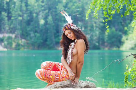 Photo for Portrait of a beautiful sexy young woman in Indian costume posing against a forest lake - Royalty Free Image